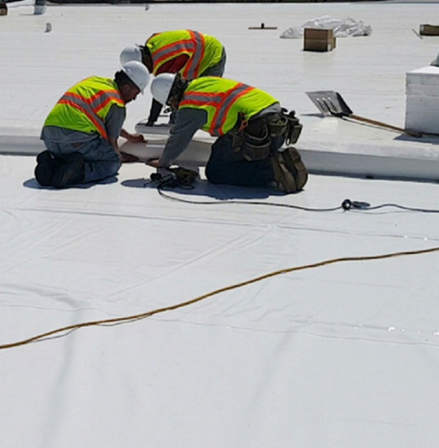 Roofers finishing a flat roof repair